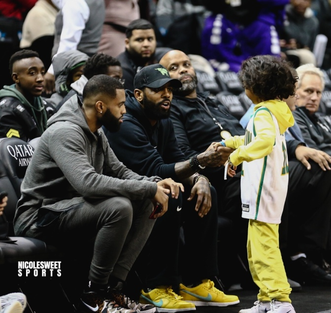 f1523ccdf076 Irving greets a young fan while sitting courtside at the Kyrie Invitational  at the Barclays Center on December 17th. (Photo courtesy of Nicole Sweet  Sports)